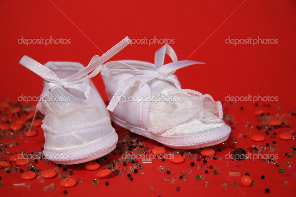 White shoes of a small child on a red background — Stock Photo #6825050
