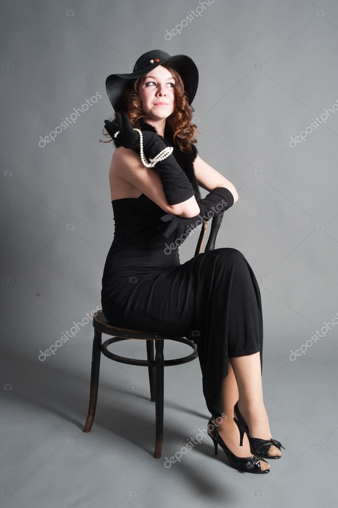 Beautiful woman in retro style dress sitting on old chair — Stock Photo #6841448