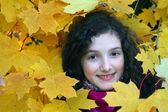 Retrato de muchacha joven hermosa con hojas amarillas — Foto de Stock