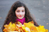 Portrait of beautiful young girl with yellow leaves — Stock Photo