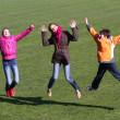Teenage girls and boy jumping on the stadium. — Stock Photo