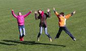Ragazze adolescenti e ragazzo saltando su stadio. — Foto Stock