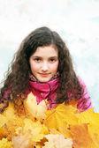 黄色叶子的漂亮年轻女孩的肖像 — 图库照片