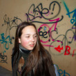 Young girl on graffiti background — Stock Photo