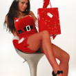 Sexy Female santa with shopping bags — Stock Photo