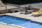 Un jeune couple au bord de la piscine — Photo