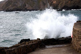 Rough sea splashing against the wall — Stock Photo