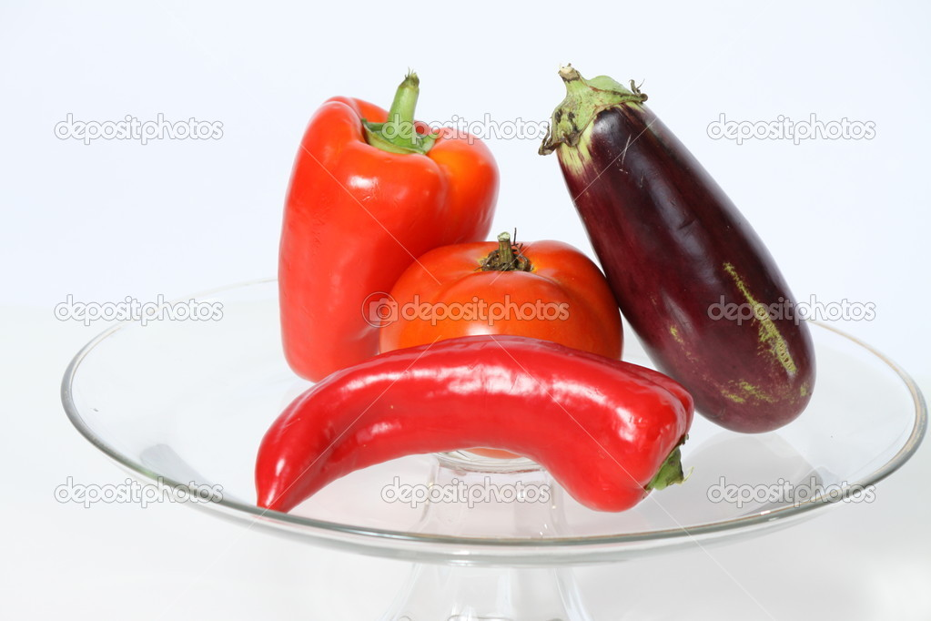 Plate with raw tomato, red peppers and egg plant from the garden — Stock Photo #6878250