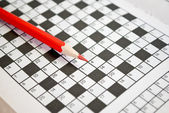 The book of crossword puzzles and red pencil. — Stock Photo