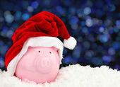 Santa Claus piggy bank on snow — Stock Photo