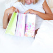 Young happy attractive girl unpack shopping bags in bedroom or h - Stock Photo