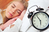 Young sleeping woman and alarm clock in bedroom at home — Stock Photo