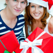 Closeup portrait of young embracing couple wearing Santa Claus h — Stock Photo