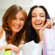 Two happy women at a shopping center with bags. Seasonal prepart — Stock Photo