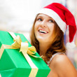 Young smiling woman holding gift standing at shopping mall weari — Stock Photo #6859018