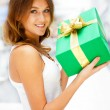Stock Photo: Beautiful brunette woman with a gift boxe standing inside shoppi