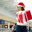 Excited attractive woman with big gift box standing at shopping — Stock Photo #6859152