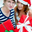 Closeup portrait of young embracing couple wearing Santa Claus h — Stock Photo #6859174