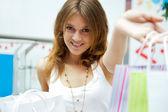 Foto de joven alegre con bolsas de compras en el fondo — Foto de Stock