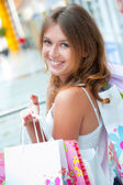 Happy shopping woman at the mall preparing gifts for her friends — Stock Photo