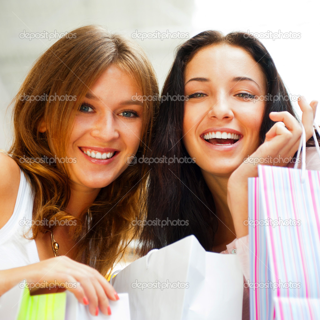 Two happy women at a shopping center with bags. Seasonal preparty shopping boom. — Stock Photo #6859009