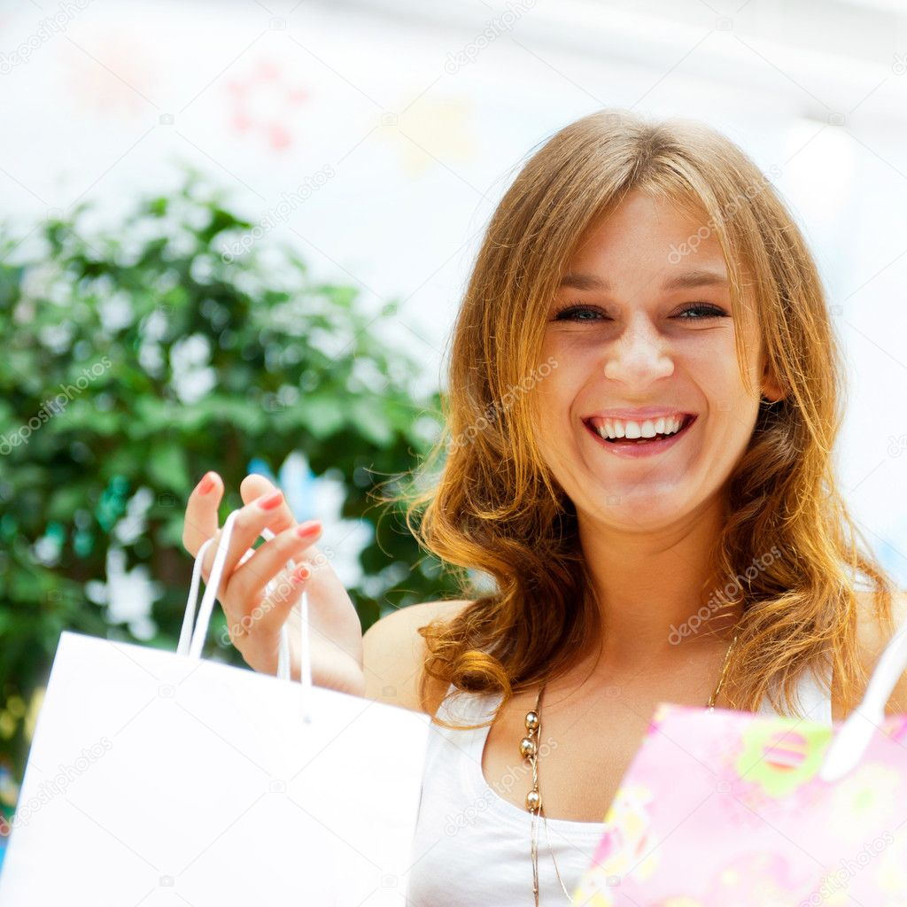 Closeup portrait of young happy woman with shopping bags at mall. Square shot. — Zdjęcie stockowe #6859012
