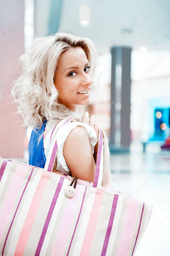 Photo of young joyful woman with shopping bags on the background of shop windows inside big mall  Stock Photo #6859019