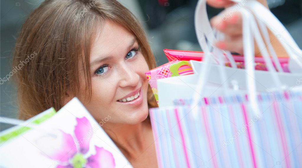 Shopping woman with lots of bags smiles inside mall. She is happy about huge christmas preseason discounts  Stock Photo #6859074