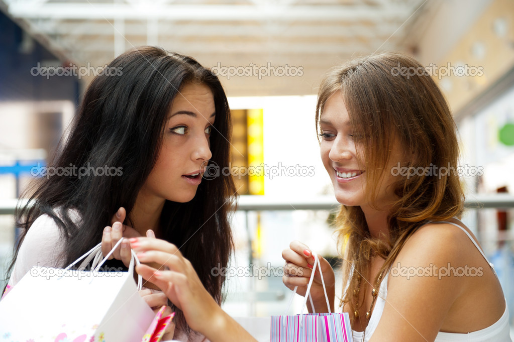 Two excited shopping woman gossip together inside shopping mall. Horizontal Shot — Zdjęcie stockowe #6859085
