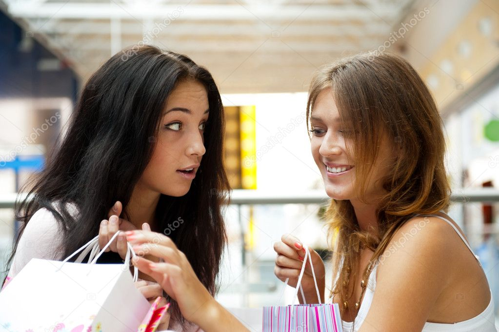 Two excited shopping woman gossip together inside shopping mall. Horizontal Shot  Foto Stock #6859085