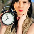 Stock Photo: Surprised woman holding alarm clock outdoors