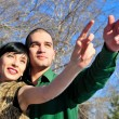 Young couple standing together in winter park, pointing and look — Stock Photo