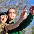 Stock Photo: Young couple standing together in winter park, pointing and look