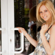 Portrait of young beautiful woman standing in front of door of h — Stock Photo
