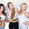 Three beautiful young women wearing sportswear inside gym hall. — Stock Photo