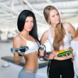 Three beautiful young women wearing sportswear inside gym hall. — Stock Photo #6872279