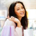 närbild porträtt av ung glad kvinna med påsar på mall — Stockfoto