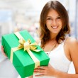 Beautiful brunette woman with a gift boxe standing inside shoppi — Stock Photo #6872495