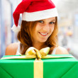 Stock Photo: Young smiling woman holding gift standing at shopping mall weari