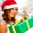 Young smiling woman holding gift standing at shopping mall weari - Stock Photo
