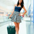 Stock Photo: Portrait of young woman walking inside modern international airp