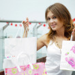 Photo of young joyful woman with shopping bags on the background — Stock Photo