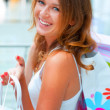 Happy woman at a shopping center with bags. Seasonal preparty sh - Foto de Stock