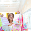 Shopping woman with lots of bags smiles inside mall. She is happ — Stock Photo #6872785