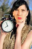 Surprised woman holding alarm clock outdoors — Stock Photo