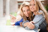 Dos hermosas mujeres bebiendo café y charlando en el café alameda. — Foto de Stock