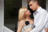 Cosy young couple embracing at home near a door and looking outs — Stock Photo