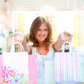 Closeup portrait of young happy woman with shopping bags at mall — Stock Photo