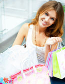 Happy woman at a shopping center with bags. Seasonal preparty sh — Stock Photo