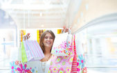 Shopping woman with lots of bags smiles inside mall. She is happ — Stock Photo